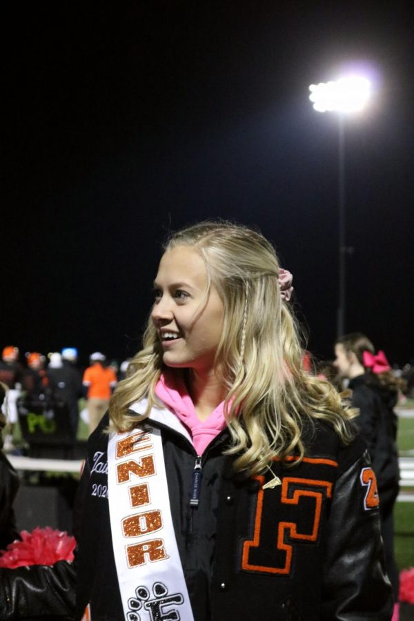 Senior Jaidyn Rogers is cheering for the Varsity football team against Walled Lake Northern. On Oct. 25, the Tigers were defeated 58-7.