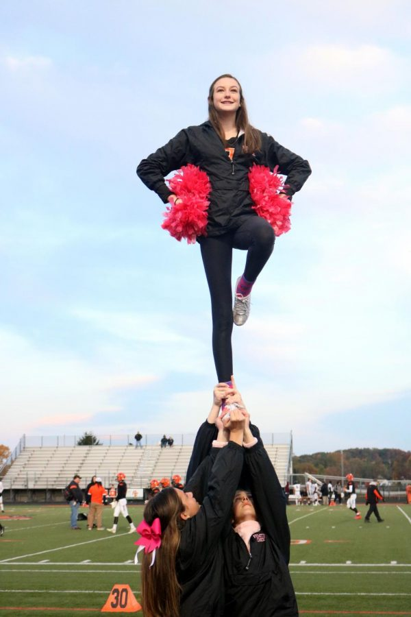 Before the game starts, sophomore Aubrey Yager does a lib with her stunt group. The girls varsity cheer team cheered at the varsity football game against Walled Lake Northern.