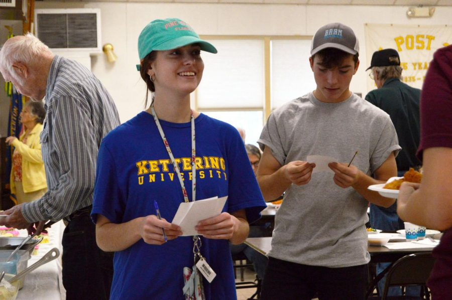 National Honors Society volunteers senior Sabrina York and sophomore Dominic Krusniak take tickets to chefs to prepare food to be taken out.  On Oct. 4, NHS students served food at Veterans of foreign Wars hall for fish fry night.
