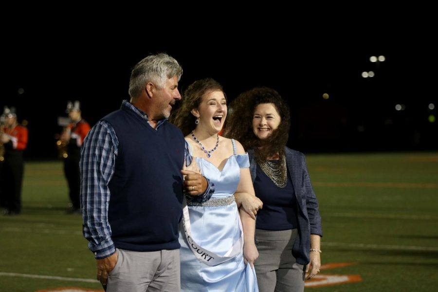 During halftime on Oct. 11, senior Jenna Maher shows her excitement as she is crowned homecoming queen. Maher and four other senior girls were on homecoming court this year.
