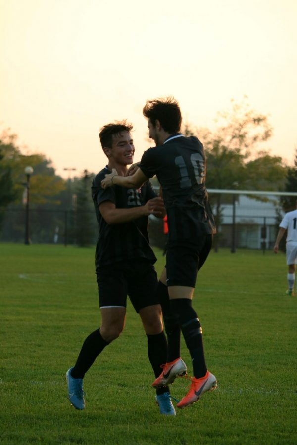 After scoring a goal, junior Nick Grigorian celebrates with senior Alex Flannery. The Tigers beat the Flushing Raiders 5-0 on Sept. 30.