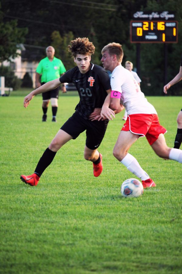 Focused in, sophomore Calvin Curtis rushes to the ball. Fenton suffered a tough defeat to Linden on Sept. 18.