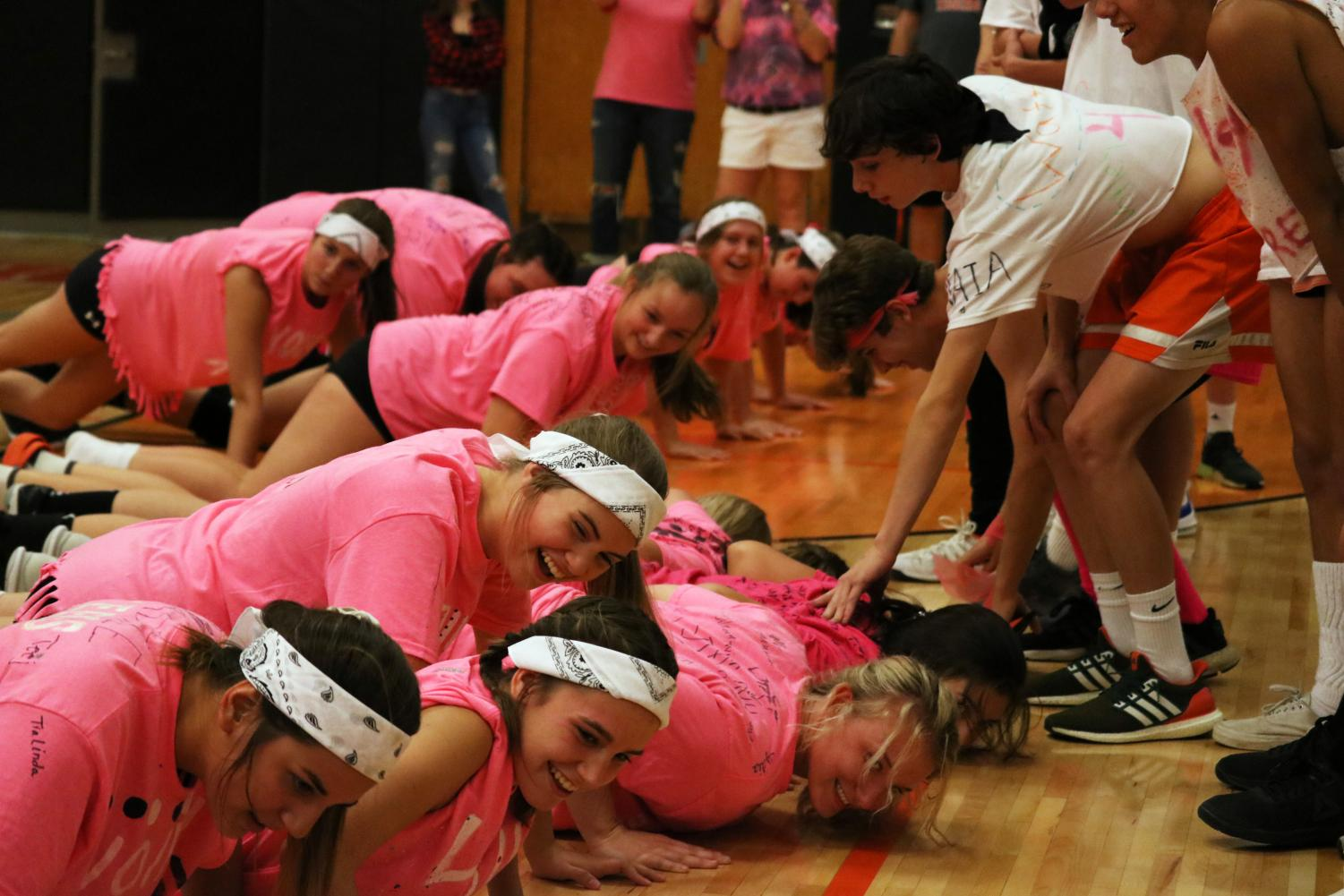 With support from the boys soccer teams, the girls volleyball teams do push ups. The two teams versed each other in a friendly game of volleyball on Oct. 10 to raise money for a Fenton student with cancer.