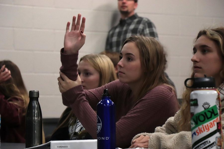 As she listens to the guest speaker, senior Ellie Koester raises her hand to ask a question. The Forensics class hosted guest speakers in the lecture hall on Nov 13.