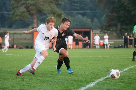 Senior Alex Flannery lunges around a player during a game against South Lyon.