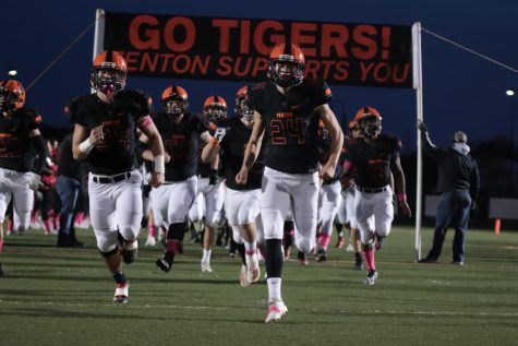 With the banner behind them, the varsity football team runs onto the field to face Walled Lake Northern High school. The tigers won this game 58-7 on Oct. 25.