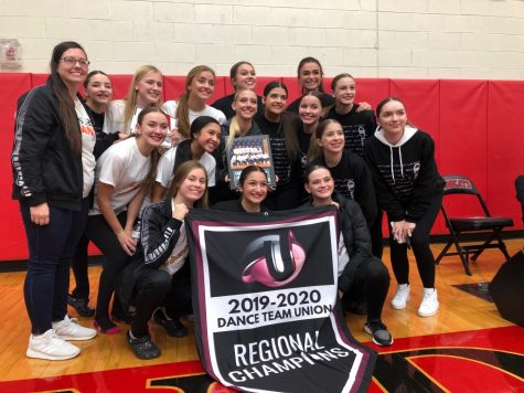 Posing for a picture, the Fenton High Adrenaline Dance team smiles with their newly won awards. The team attended a competition on Nov. 2 at Grand Blanc High School.