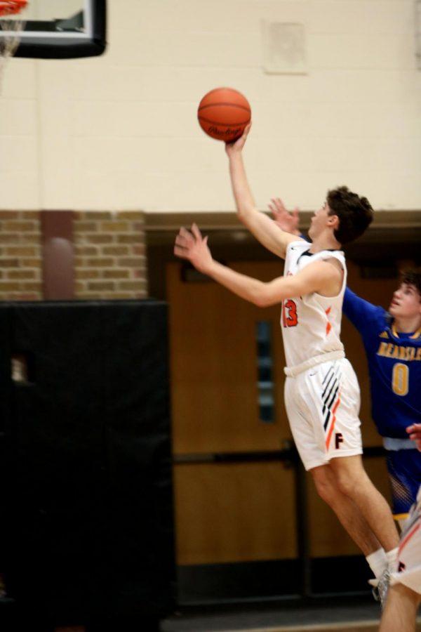 Sophomore Henri Sturm jumps towards the basket with the ball. On Jan. 9, the Fenton JV Basketball team won against Kearsley.
