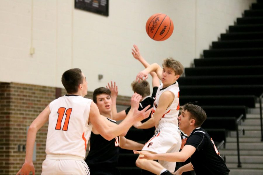 Sophomore Austin Pedlar blocks the ball from going into the other teams basket. On Jan. 28, the Fenton Tigers JV basketball team won against Clio.