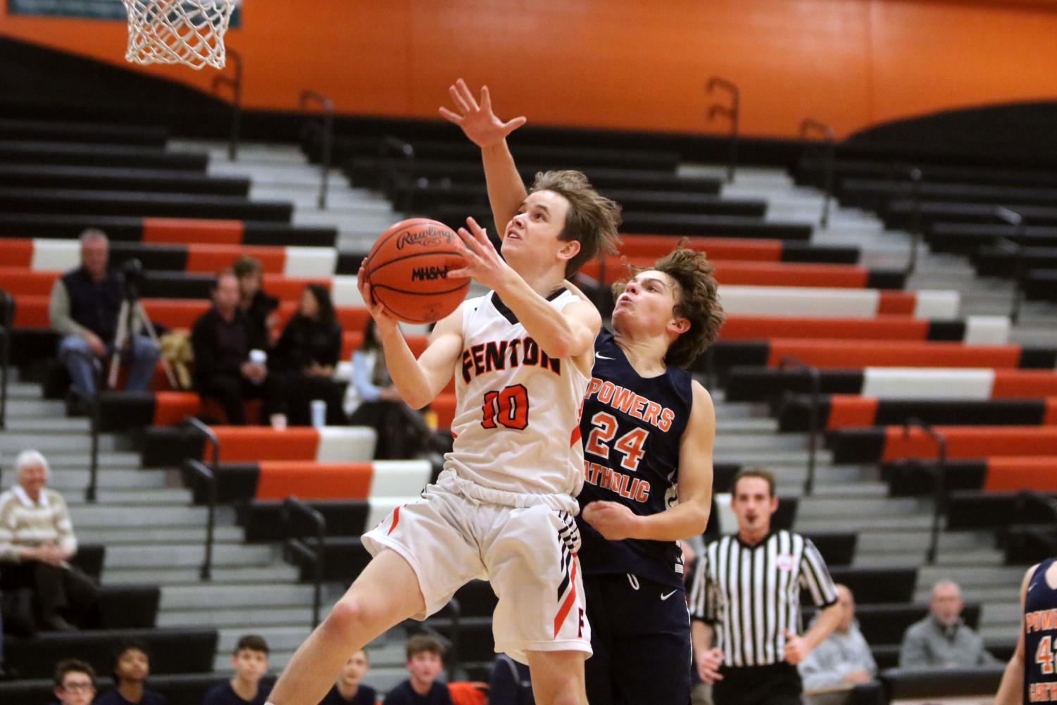 Freshman Ayden Gray jumps for the hoop hoping to make a shot. On Jan. 10 Fenton won 48-47 against Kearsley in a close game.