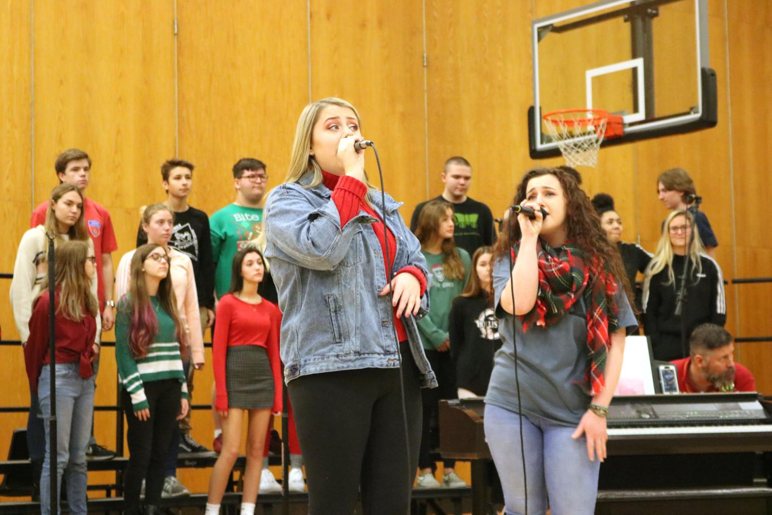 Seniors Jenna Maher and Autumn Decker sing Christmas songs in front of the student body, accompanied by the jazz band. On Dec. 20, the holiday concert was held in the main gym during SRT to get students in the holiday spirit.