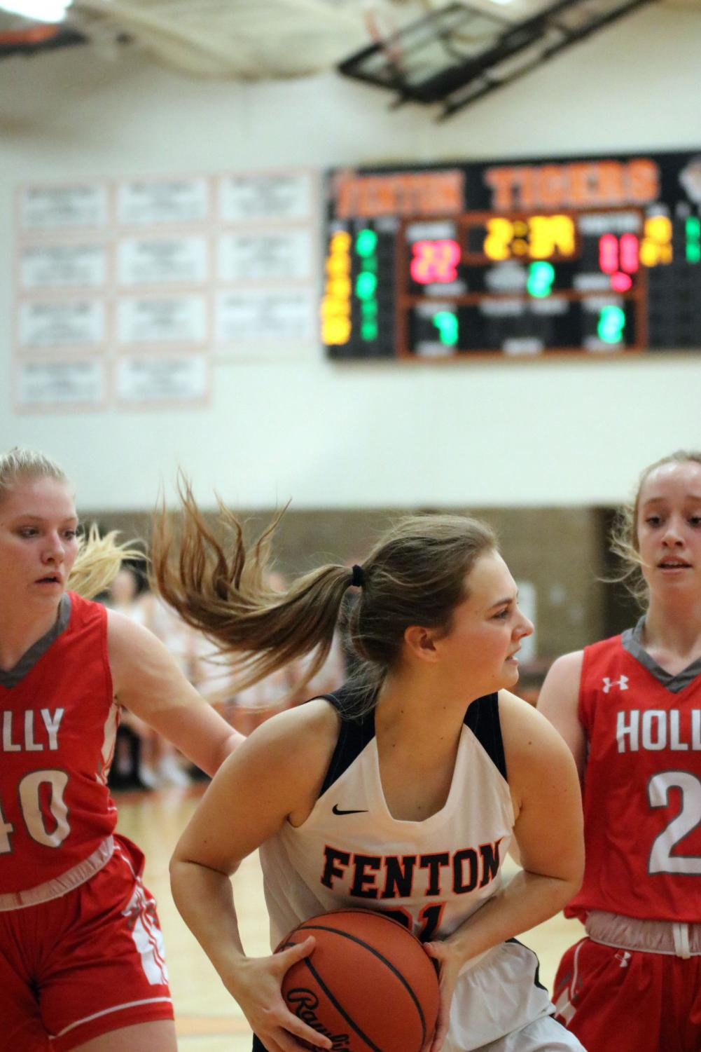 Guarding the ball from her opponents, senior Erica Behnfeldt looks for a teammate to pass to. On Dec. 20, the girls varsity basketball team played Holly at home, winning 50-44.