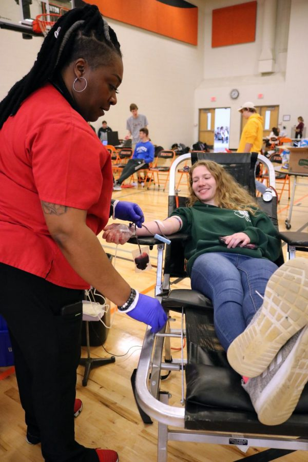 Smiling during a conversation with a nurse, senior Eileen O'Rourke gets her blood drawn. On Jan. 10, students ages 16 or older had the opportunity to donate blood.