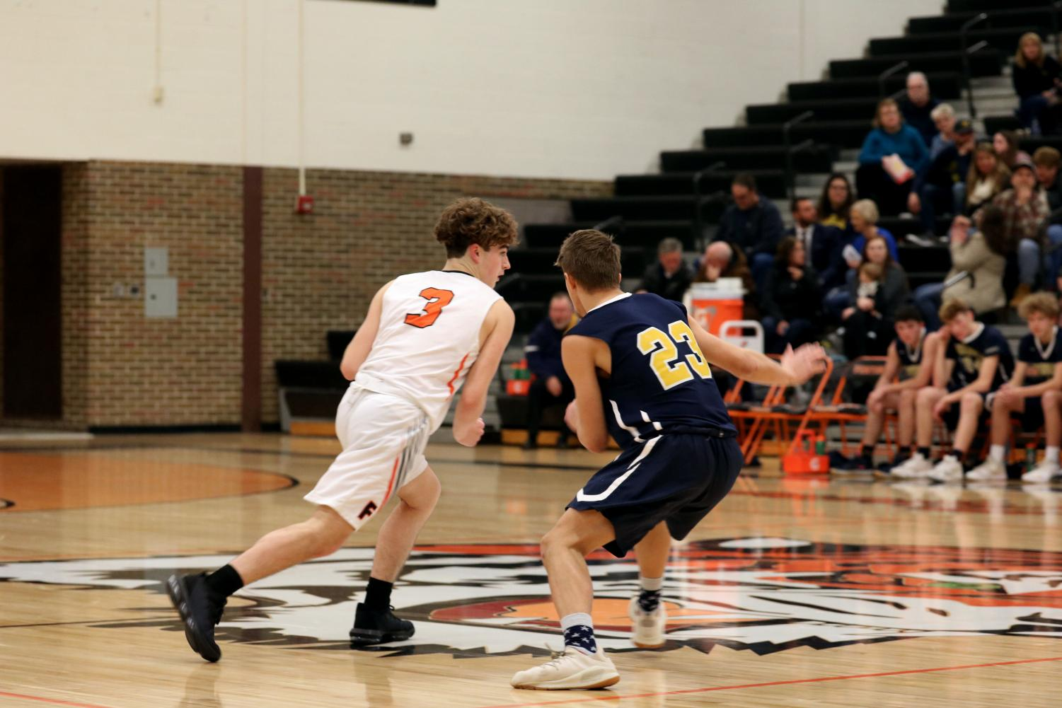 Sophomore Calvin Curtis dribbles the ball to the basket from the defender. On Jan. 7, the Fenton Tigers JV boys basketball team won against Goodrich.