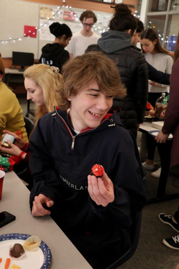 While at the yearbook Holiday Party, junior Logan Reeves eats a cupcake that was brought in by a fellow classmates. On Dec. 20 the yearbook class had a party where they exchanged secret Santa gifts and ate.