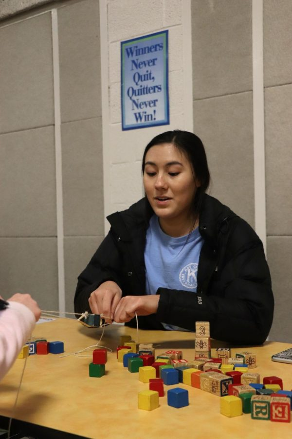 While volunteering for the Family Science and Nature Night at North Road Elementary, senior Cassie North pulls on strings to help a child stack the blocks. On Jan. 21, North Road hosted the event where Key Club and NHS students volunteered to help young children and students learn more about science and nature.