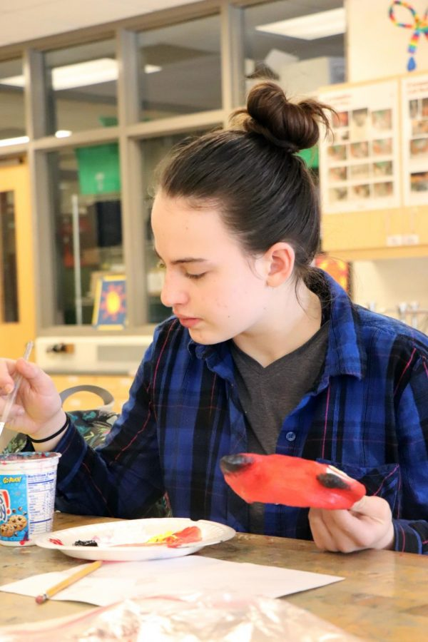 Completing her paper mache mask, sophomore Annabeth Carnes, paints it into a fox. The art class was doing a project on making Indian style masks in the shape of an animal.