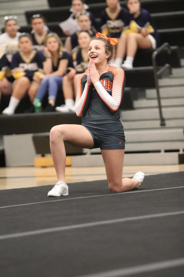 Cheering at a competition, freshman Sophie Pasienza smiles at the judges. On Feb. 8 the Fenton varsity cheer team hosted a competition.