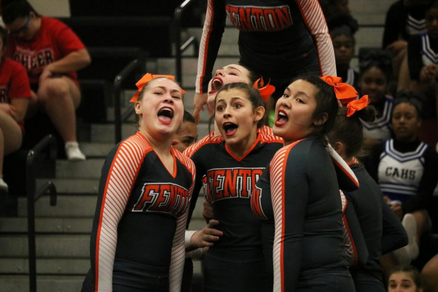 During round three of their competition, freshman April Carr, sophomore Laura Singer and senior Lilian Huynh perform their stunts. The varsity competitive cheer team took 2nd place in division two on Feb. 8.