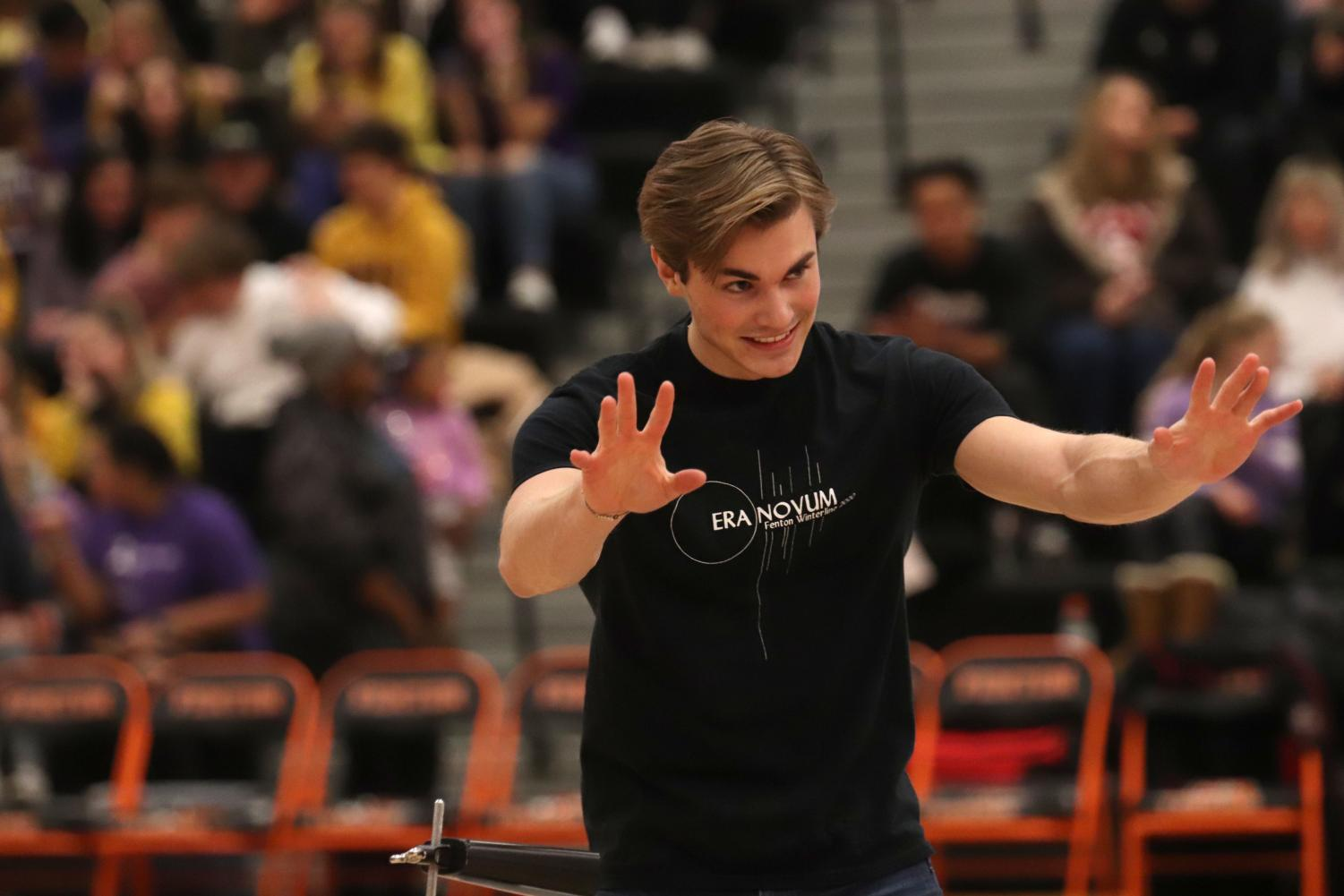 After performingwoth the drumline, senior Andrew Donar waves to the audience. The drumline perfomed during both the girls and boys varsity basketball games on Jan. 31.