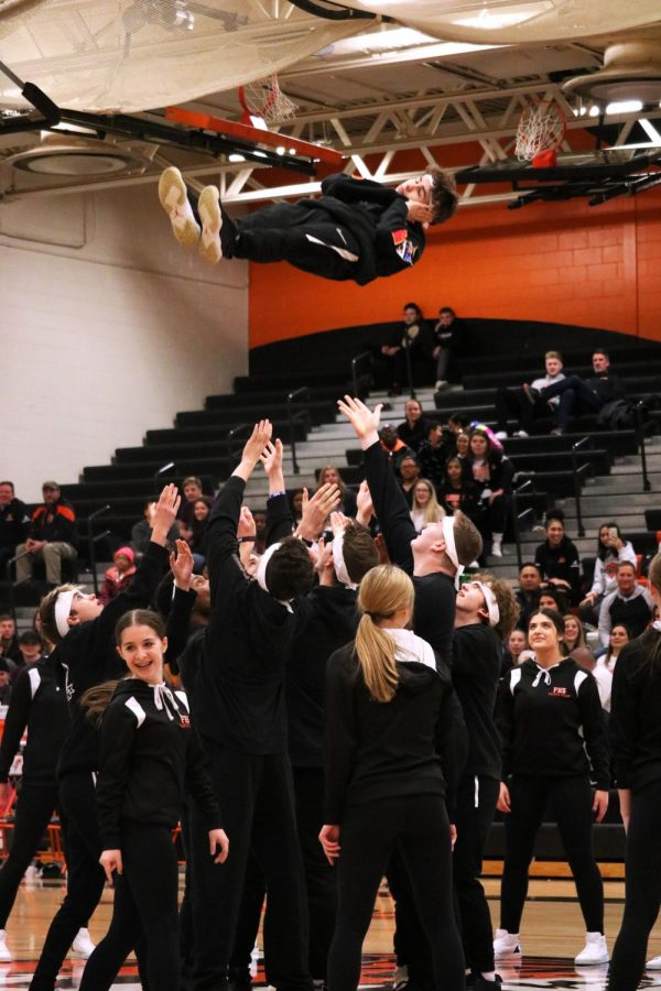 Being thrown in the air, sophomore Lucah White pretends he's asleep during the performance. On Feb. 28, the dance team asked some other students to join them for the last basketball game halftime.