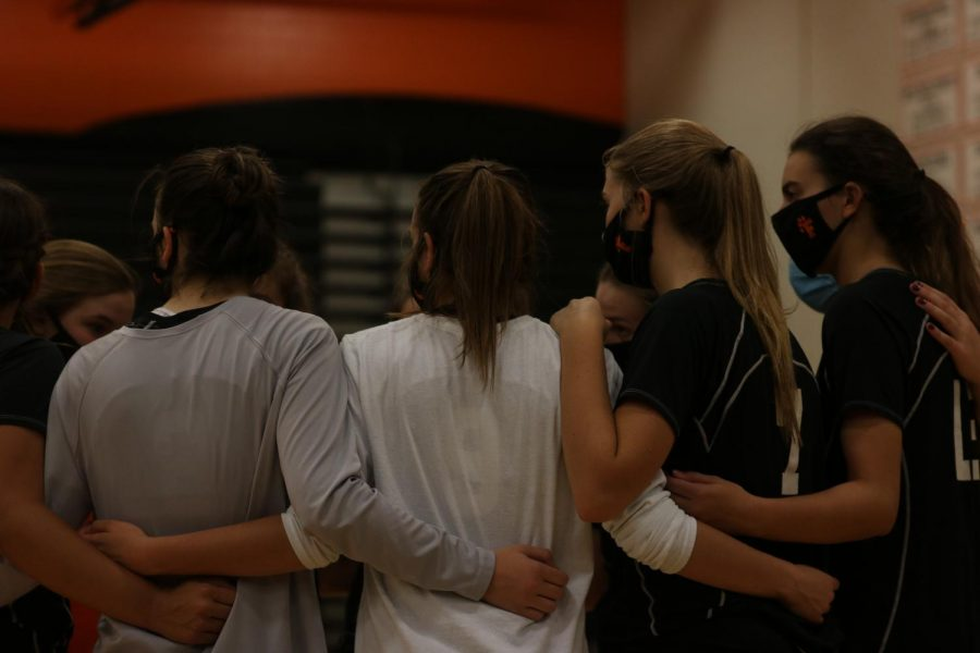 JV volleyball girls talking a quick huddle before the match. the girls played hard and brought their team to victory.