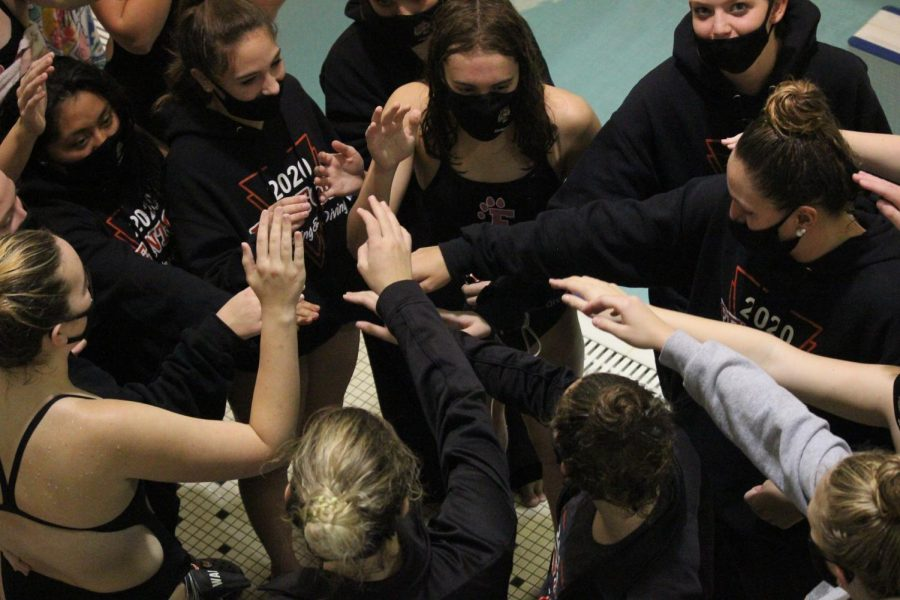 Putting their hands together, the varsity girls swim team celebrate their win against Kearsley. The Tigers came out victorious ___.