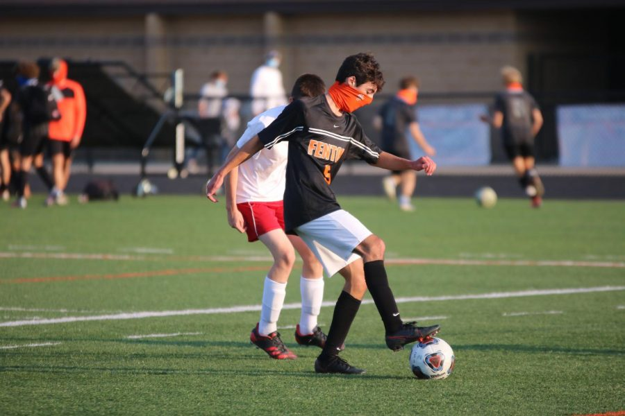 Sophomore Ryan Stocker stops the ball from going out of bounds. On Sept. 24, the Tigers won against holly with a score of 5-0.