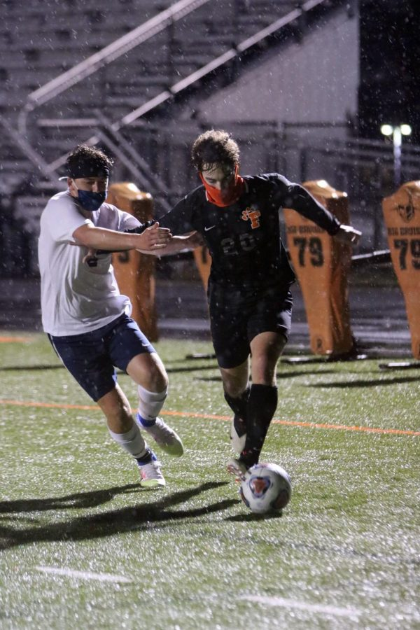 Running through the rain, junior Calvin Curtis dribbles the ball while avoiding an opponent. On Sept. 30, the Tigers played Goodrich at home, winning 3-1.