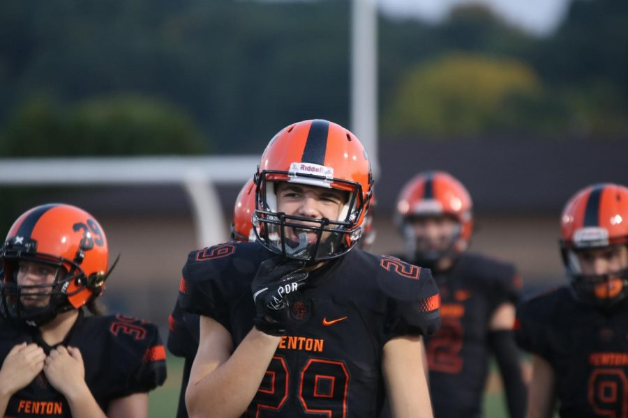 Junior Daniel Mott ready himself for the game with his safety equipment such as his mouth guard. Mott and the team played Sept. 25 and won 50 - 14 against Kearsley.