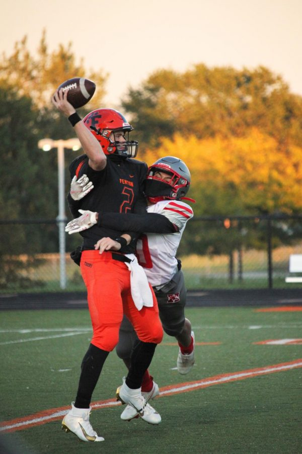 While being tackled, senior Dylan Davidson throws a pass to a teammate. Fenton defeated Holly 46-0.