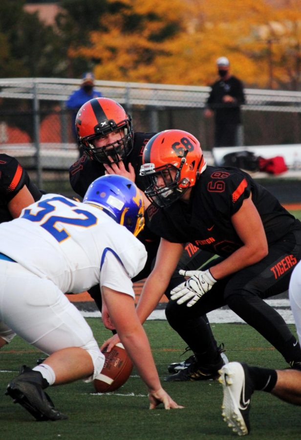 Staring down an opponent, senior Logan Fuller prepares tp hike the ball. On Sept. 25, the Tigers came out victorious in their Homecoming game against Kearsley 50-14.