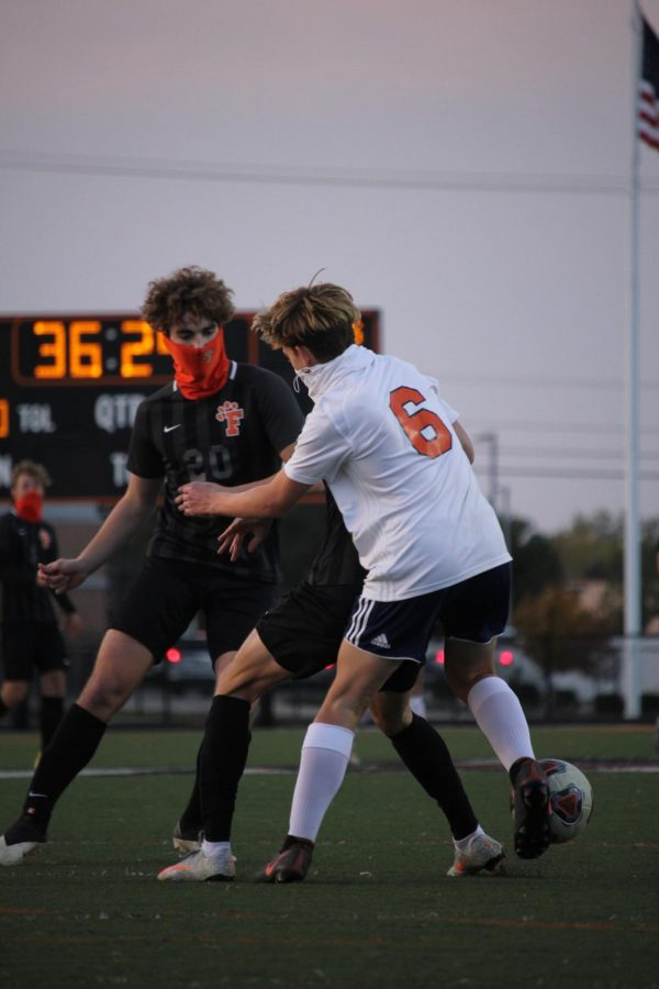 Junior Calvin Curtis defends an opponent from Powers. On Oct. 9, the Tigers came out on top 2-0.