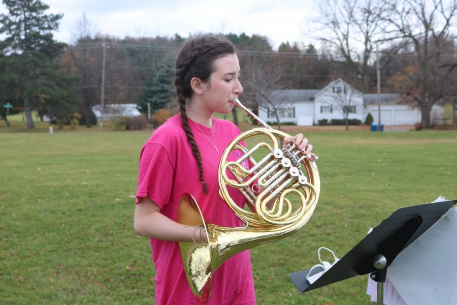 Sophomore Keira Shantry practices her mellophone outside during sectionals in Symphony Band this morning. Mr. Conaton