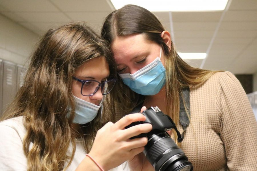 Sophomore Maddie Slezinski helps sophomore Adrie Staib with the settings on her camera. The photographers on the Fentonian Yearbook staff do walk arounds the school to find photo opportunities.