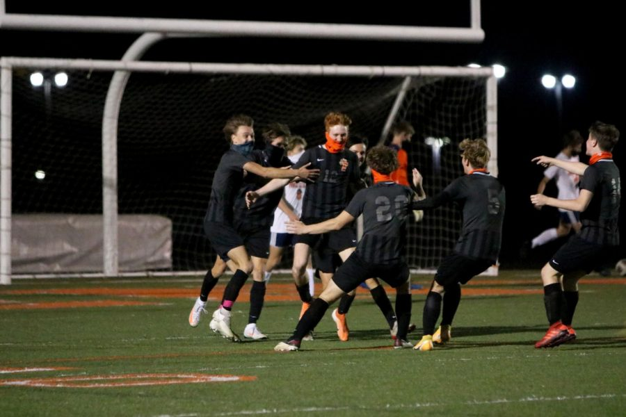 Senior Andrew Hutchins celebrates with his team after scoring a goal for the Tigers. On Oct. 9. the Fenton varsity boys soccer team defeated Powers 2-0.