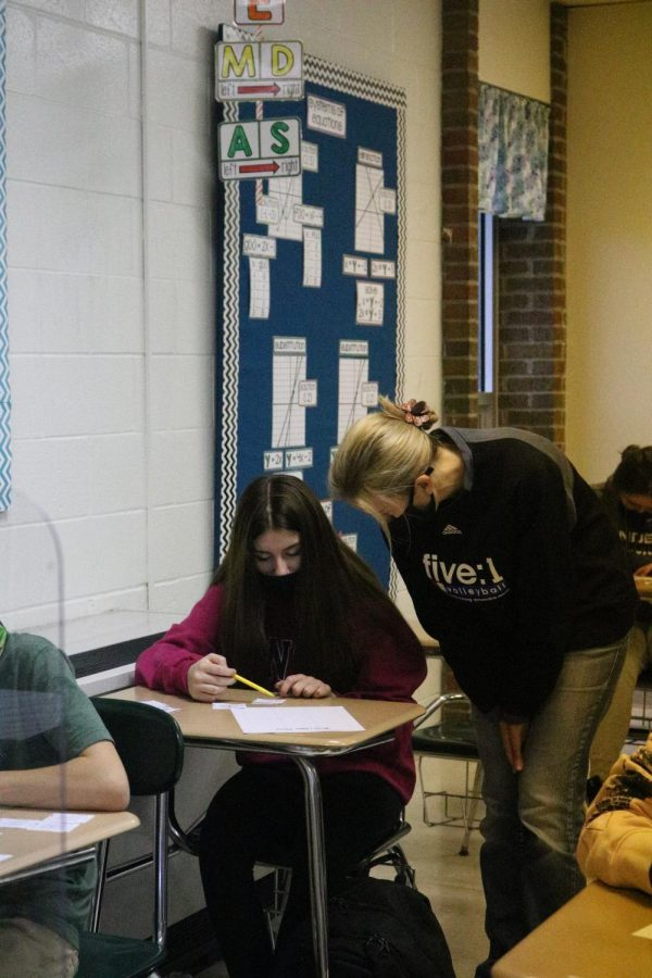 Freshman Sunny Wilkinson asks Mrs. Sahr a question in algebra 1 class. On Nov. 13 Sahr's class worked on puzzles.