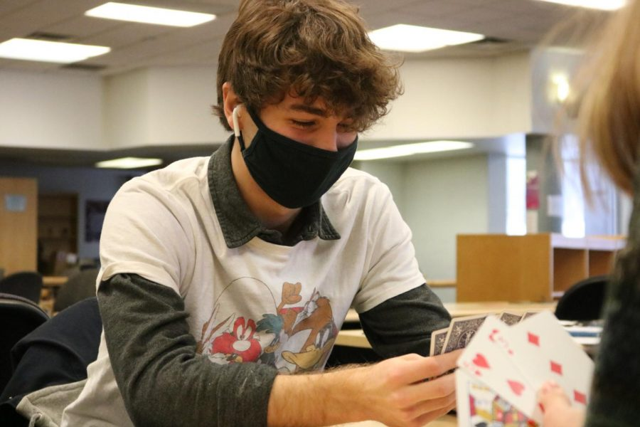 Junior Lucah White plays go fish with his friend. On Feb. 12, White played card games with friends in the media center.