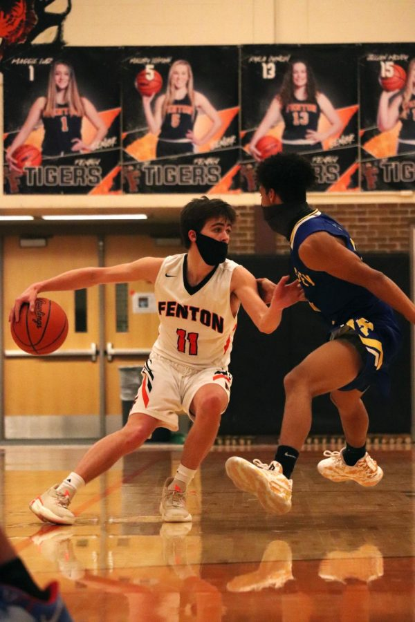 Considering his next move, senior Gavin Shepherd looks for an open teammate. On Feb. 19, the Tigers defeated the Kearsley Hornets in a tight game 52-50.