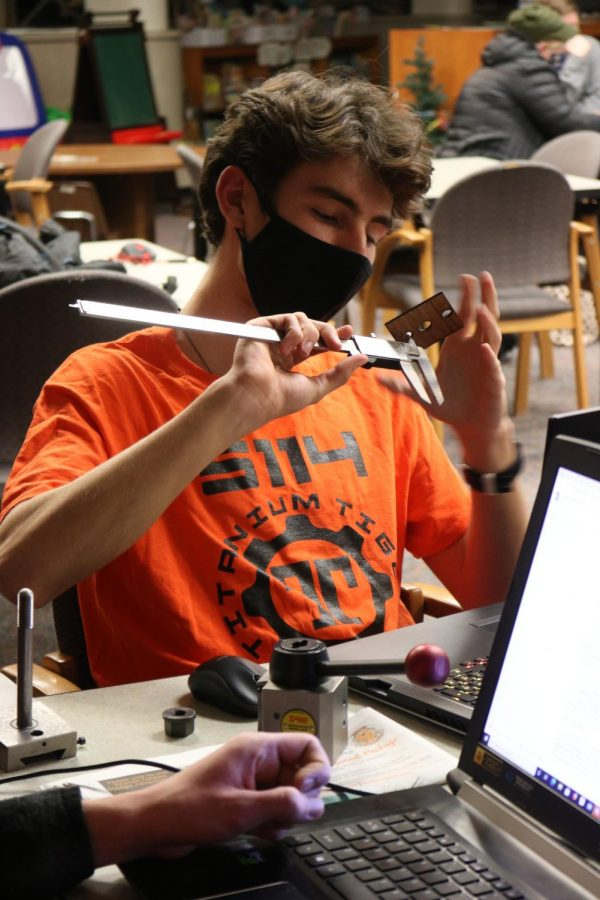Senior Brody Stack works on measuring a part for the Robotics team robot.