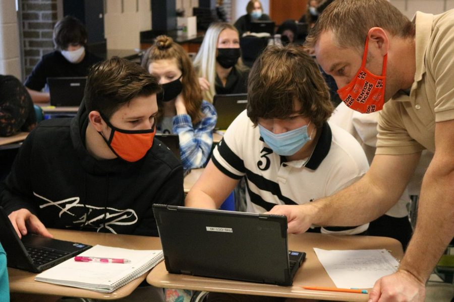 Freshmen Parker Muntin and Christopher Curtis recieve help from a teacher on their assignment.