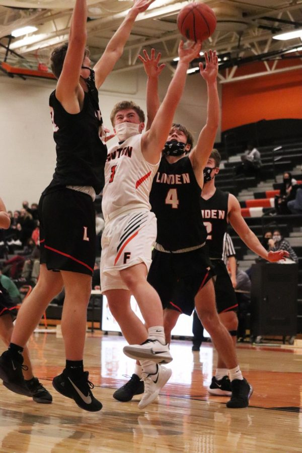 Surrounded by opponents, junior Connor Luck goes to make a basket. On Feb. 23 the Tigers were defeated by their rival, the Linden Eagles.