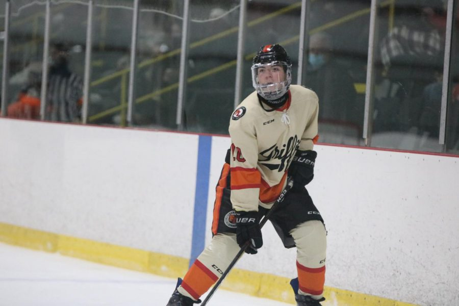 Searching for a teammate to pass to, senior Dominic Kruzniak skates towards the opposing goal. On February 10, the varsity hockey team played Oxford at home.