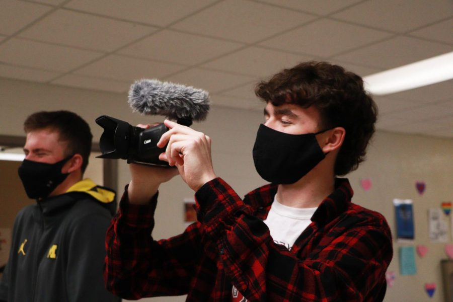 During video productions, sophomore Charlie Weir practices interviewing students around the building.