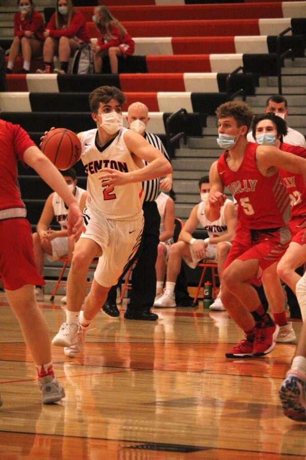 Doing his best to avoid Holly opponents, Junior Seth Logan charges to the basket on Feb. 17. The Tigers defeated the Broncos 51-45.