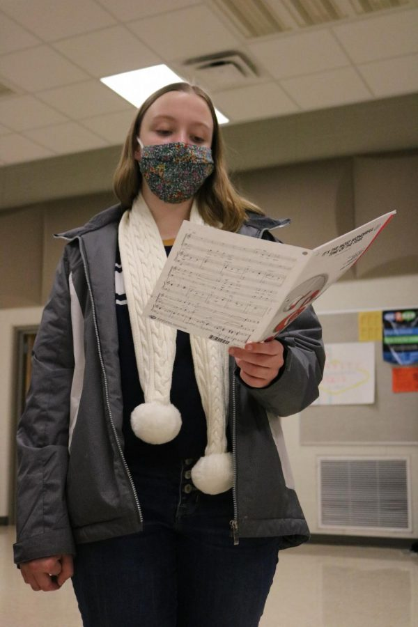 Freshman Macy Wright reads her lines off her music sheet as she sings. On November 16, the Ambassadors had rehearsal and practiced their songs.