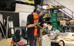 With sparks flying, seniors Shawn Defina and Brody Stack grind down a piece of steel. The Fenton Robotics team meets every Tuesday and Thursday.