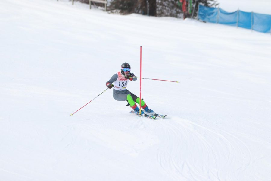 Going around a gate, junior Chase Gibson races down the hill. On Feb 10 the Alpine Ski Team competed at regionals.
