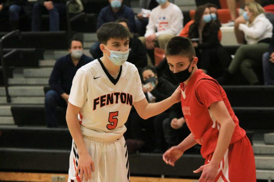 Freshman Alec Coenen guarding a Swartz Creek Dragon during the JV basketball game.