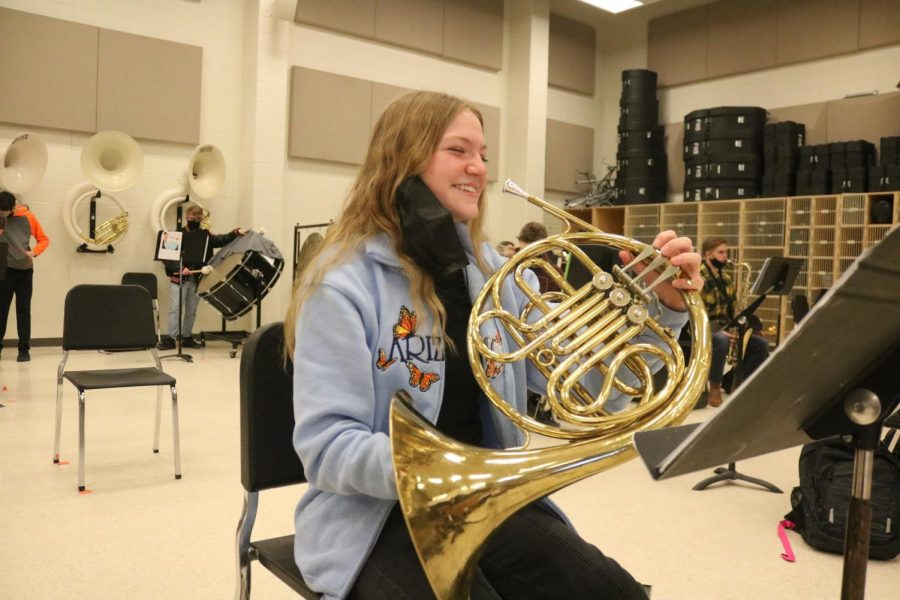 Freshman Julia Blanchard smiles before playing her French horn. On Feb. 18, the 2nd hour band class practiced their pieces together.
